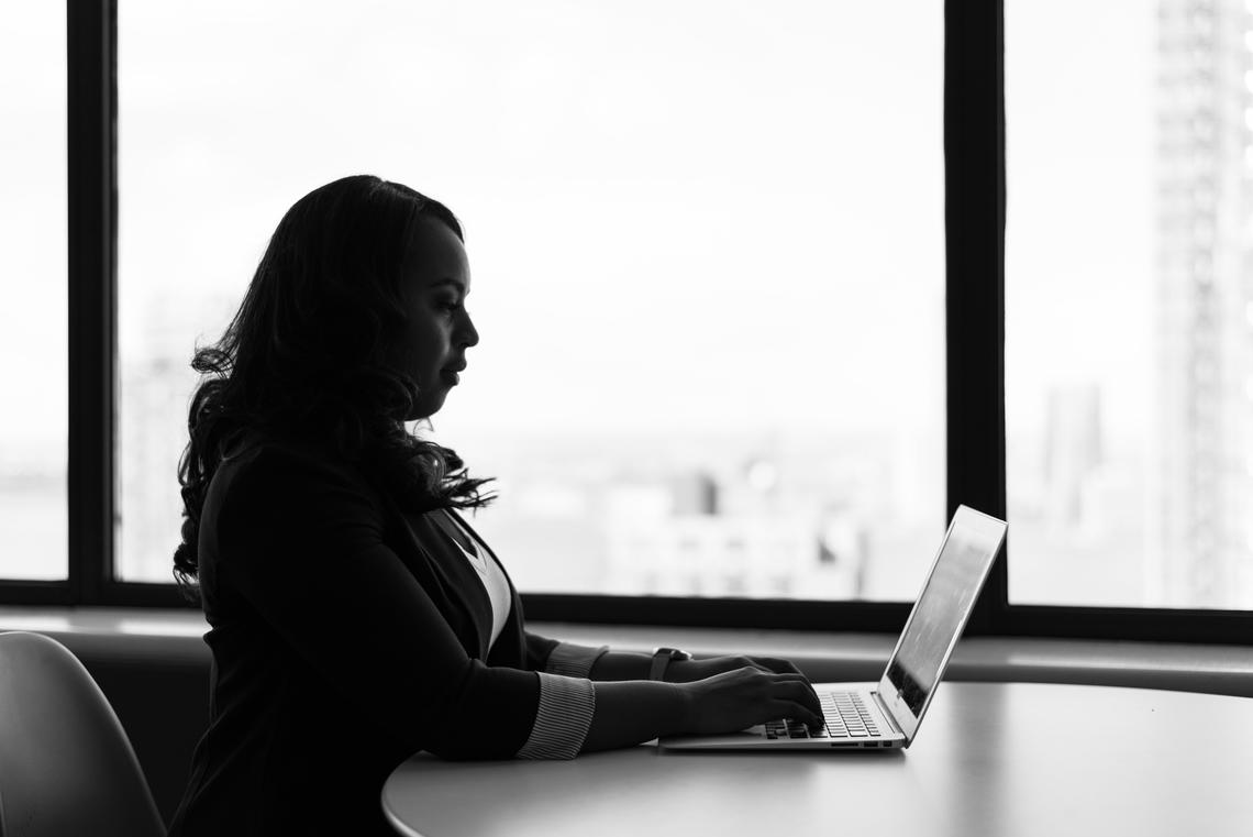 Woman sitting in front of a laptop in front of windows overlooking a city.