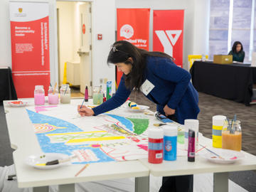 Dr. Veronica Caparas, Faculty of Social Work, adds her artistic contribution to a mural participants collaboratively painted throughout Knowledge to Impact: Igniting Community Engagement in the City Building Design Lab.