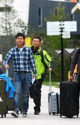 Students with suitcases come to campus