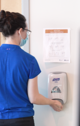A woman uses a wall mounted hand sanitizer dispenser